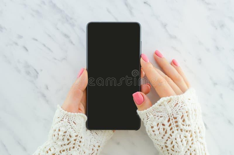 Kvinnahänder som rymmer smartphonen på, marmorerar bakgrund med kopieringsutrymme Lekmanna- lägenhet Top beskådar Kvinna som anvä royaltyfri fotografi