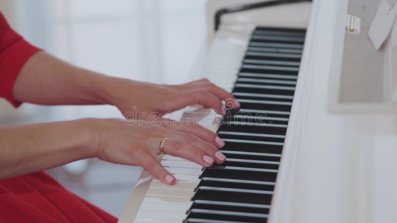 Kvinnahänder som spelar pianot arkivbilder
