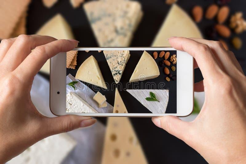Kvinnahänder som tar ett foto av olika sorter av ostar på svartstenbräde med muttrar och örter arkivbild