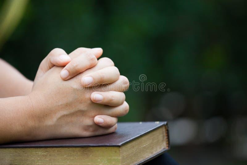 Kvinnahänder vek i bön på en helig bibel för trobegrepp royaltyfria foton