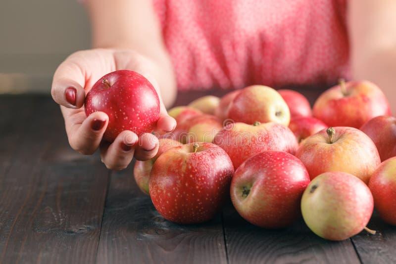 Kvinnahålläpplen på träbakgrund arkivfoton