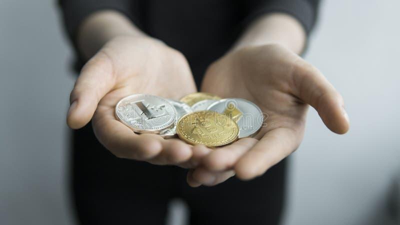 Kvinnahåll i fysiska guld- cryptocurrencymynt för händer - och försilvrar bitcoins-, ethereum- och silverlitecoin vinst royaltyfri fotografi