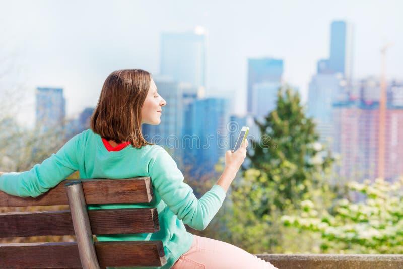 Kvinnahållmobiltelefon med Seattle som är i stadens centrum på baksida arkivfoton