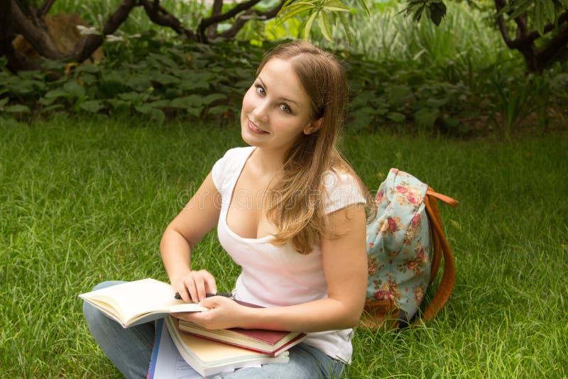 Kvinnahögskolestudenten med boken som in studing, parkerar royaltyfria bilder