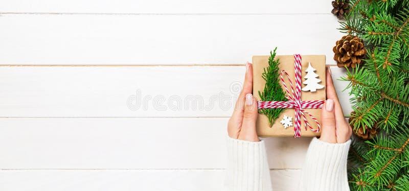 Kvinnah?nder ger sl?gen in jul handgjord g?va i papper med julgarnering Närvarande ask på ferie på banermörker fotografering för bildbyråer