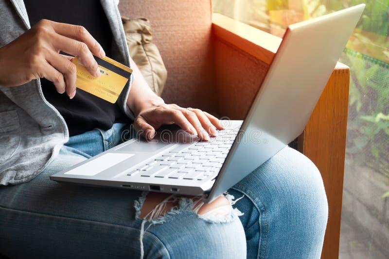 Kvinnah?nder med b?rbara datorn och kreditkorten som direktanslutet shoppar Betalningtransaktion p? datoren genom att anv?nda kre arkivfoton