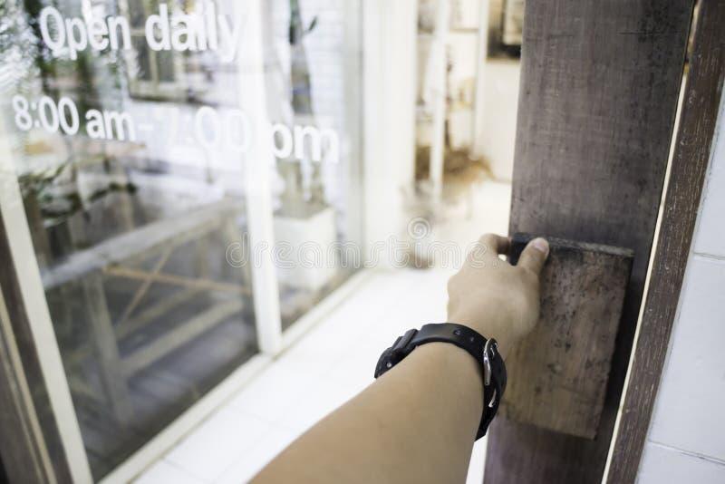 Kvinnahandöppningen shoppar dörren royaltyfria foton