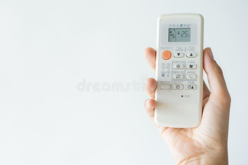 Kvinnahand genom att använda öppen luft för fjärrkontroll som betingar 25 grader Öppen luft 25 grader, är temperaturen royaltyfria bilder