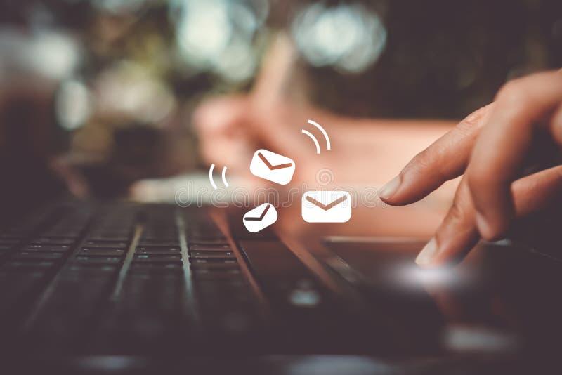 Kvinnahand genom att använda bärbara datorn för att överföra och motta emailen royaltyfri bild