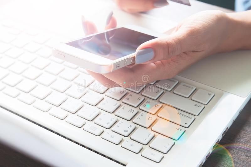 Kvinnahand genom att använda mobila enheten och bärbara datorn på hennes skrivbord, online-shopping royaltyfria foton
