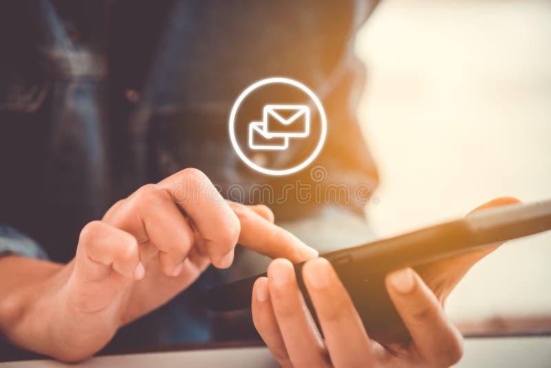Kvinnahand genom att använda smartphonen för att överföra och motta emailen royaltyfri bild
