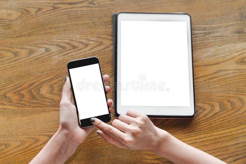 Kvinnahand genom att använda smartphonen med den tomma skärmen och den digitala minnestavlan arkivbilder