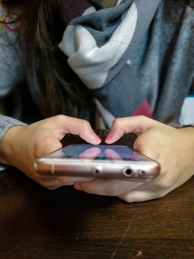 Kvinnahand genom att använda smartphonen på kafeterian Ung kvinnlig som använder den smarta telefonen på restaurangen royaltyfri fotografi