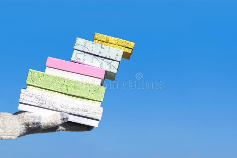 Kvinnahand i de stack handskarna med många gåvaaskar på bakgrunden för blå himmel Begrepp av den säsongsbetonad eller vinterrabat fotografering för bildbyråer