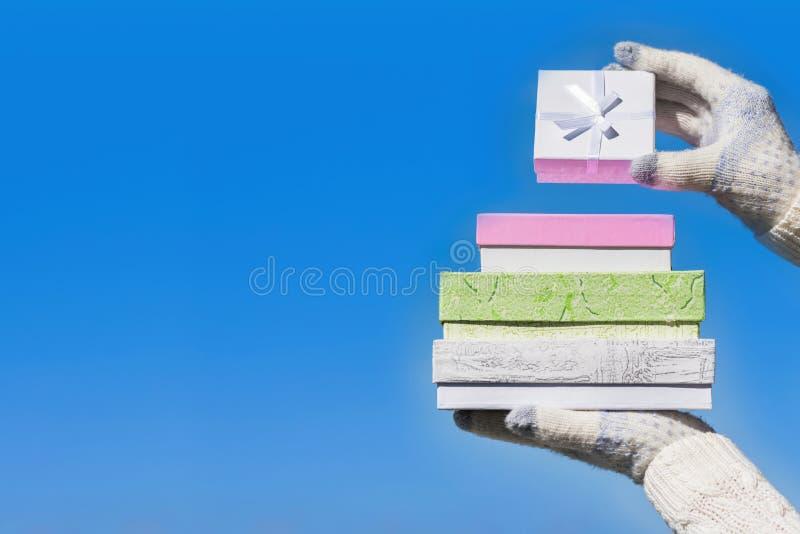 Kvinnahand i de stack handskarna med många gåvaaskar på bakgrunden för blå himmel Begrepp av den säsongsbetonad eller vinterrabat royaltyfria foton