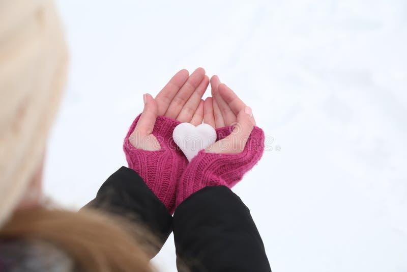 Kvinnahand i woolen handskar som rymmer snöhjärta fotografering för bildbyråer