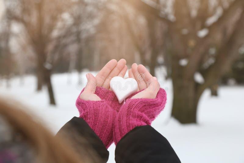 Kvinnahand i woolen handskar som rymmer snöhjärta arkivfoto