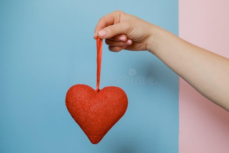 Kvinnahand med en hjärta på rosa färg- och blåttbakgrund Valentin` s royaltyfri foto