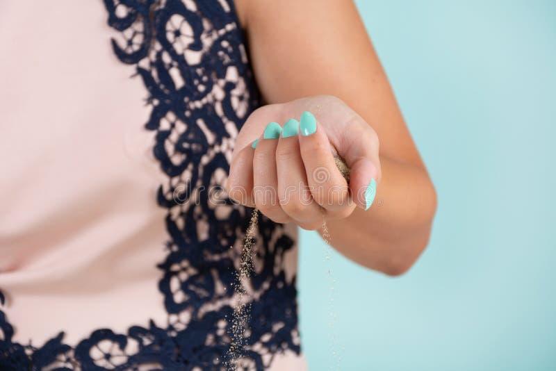 Kvinnahand med en sand för hav för innehav för turkosfärgmanikyr och sanden som läcker från handen i studion royaltyfri fotografi