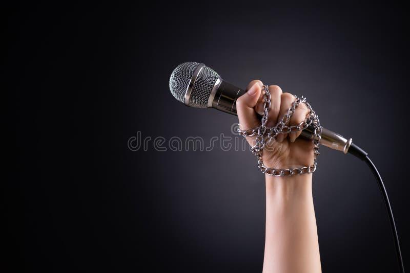 Kvinnahand med mikrofonen som binds med en kedja och att visa idén av tryckfrihet eller yttrandefrihet på mörker royaltyfri bild