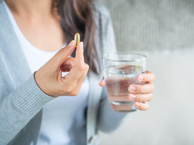 Kvinnahand med preventivpillermedicinminnestavlor och exponeringsglas av vatten i henne arkivfoto