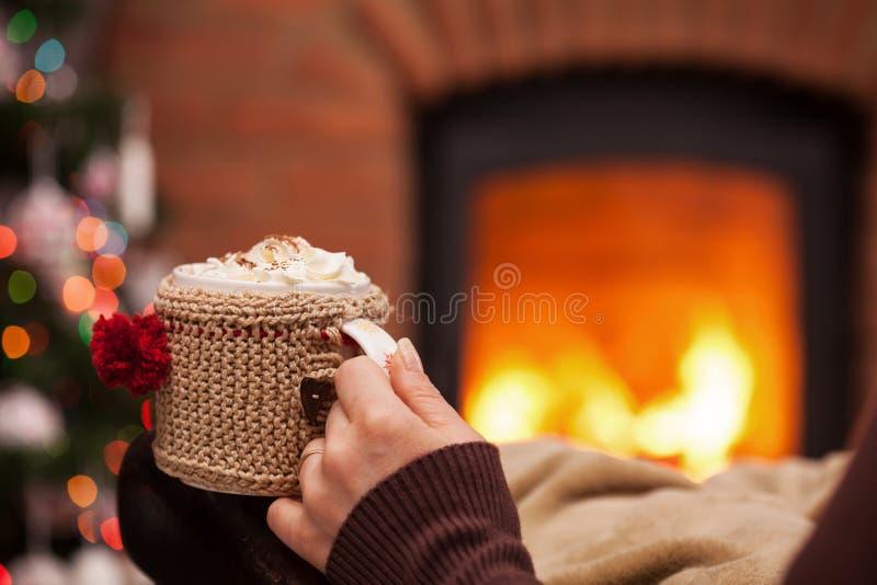 Kvinnahand på fåtöljen med en kopp av varm choklad som framme vilar av spisen och julträd arkivbilder