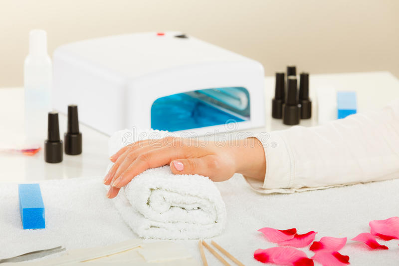 Kvinnahand på handduken, bredvid manikyruppsättning arkivbilder