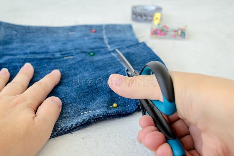 Kvinnahand rymma sax och klippa jeanskortslutningar som gör dem kortare Framställning av grov bomullstvillkortslutningar P? en vi royaltyfria foton