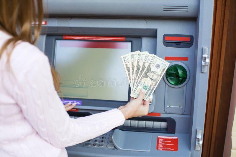 Kvinnahand som återtar pengar från den utomhus- banken ATM arkivfoto