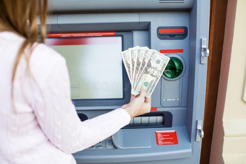Kvinnahand som återtar pengar från den utomhus- banken ATM royaltyfria bilder