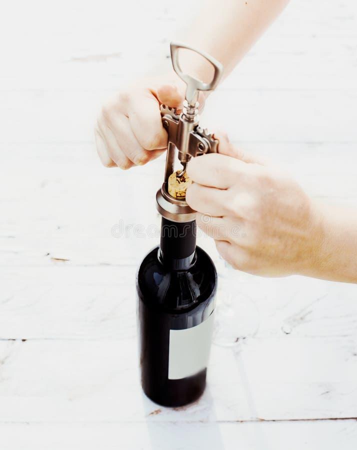 Kvinnahand som öppnar en flaska av rött vin med korkskruvet på gammal w royaltyfri bild