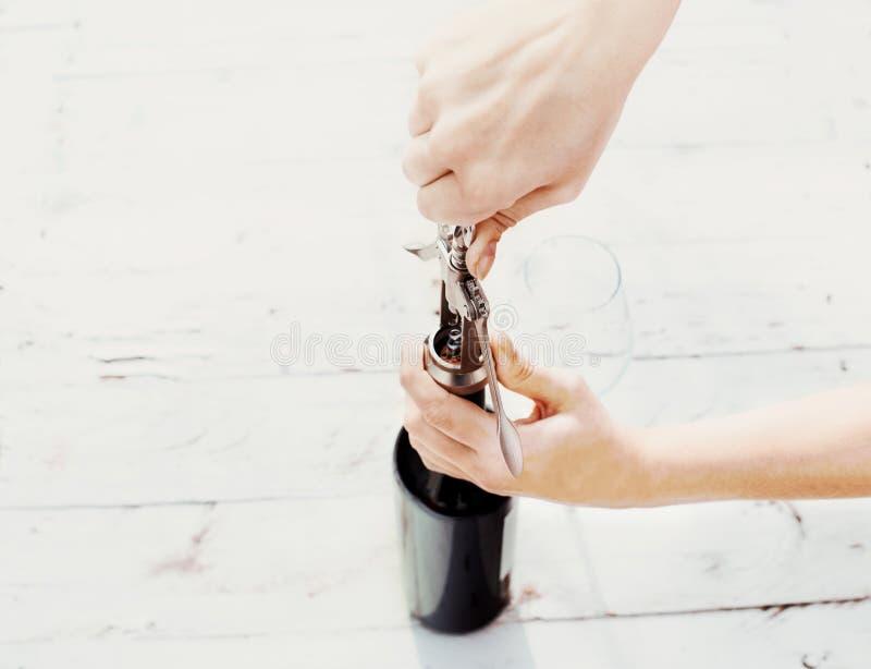 Kvinnahand som öppnar en flaska av rött vin med korkskruvet på gammal w fotografering för bildbyråer