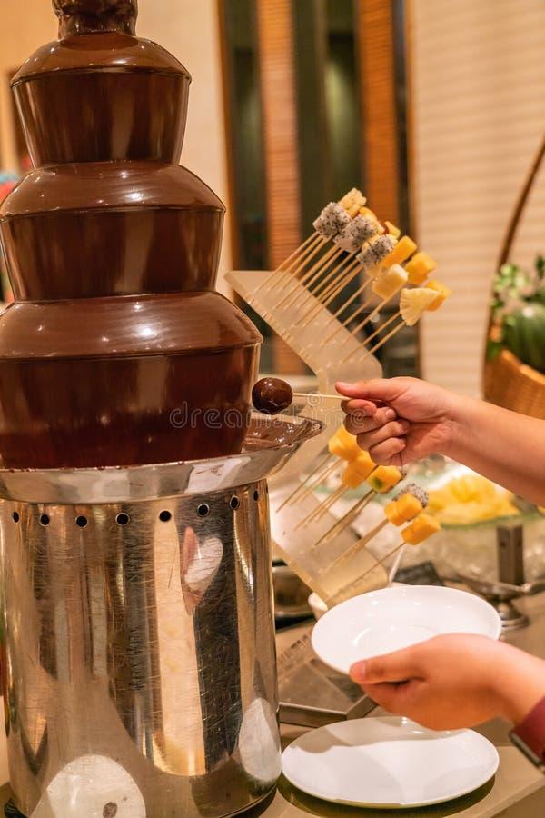 Kvinnahand som doppar frukt till chokladtornet arkivfoto