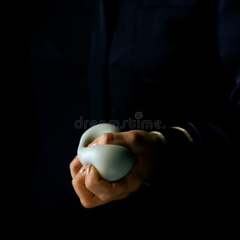 Kvinnahand som isoleras på svart genom att använda anti-spänningsbollen arkivfoto