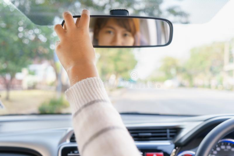 Kvinnahand som justerar spegeln för bakre sikt av hennes bil royaltyfri fotografi