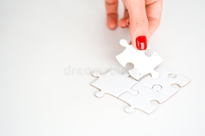 Kvinnahand som passar det högra stycket av pusslet som föreslår affärsnätverkandebegrepp arkivbild