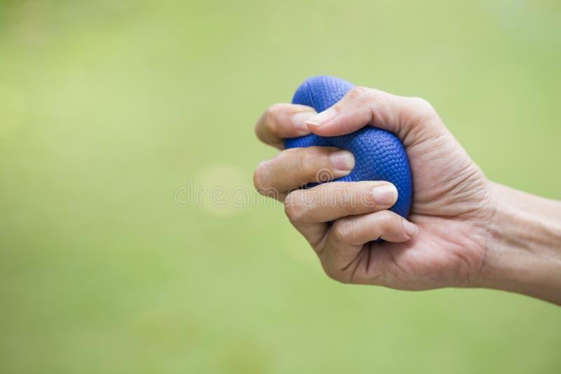 Kvinnahand som pressar en spänningsboll royaltyfria bilder