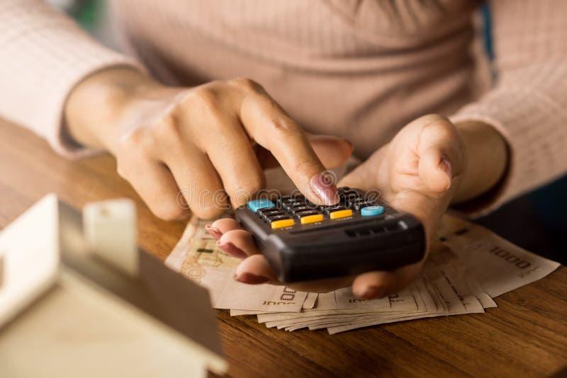 Kvinnahand som räknar pengarbakgrund som hyvlar för att köpa eller hyra hem med räknemaskinen, suddighetshusmodell på trätabellen royaltyfri foto