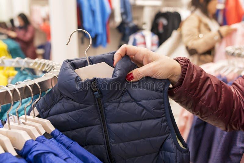 Kvinnahand som rotar i klädlagret, consumerismbegrepp royaltyfri bild