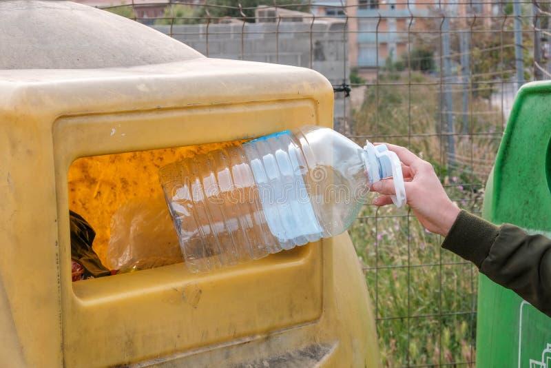 Kvinnahand som rymmer den tomma stora plast- flaskan in i behållaren royaltyfri bild