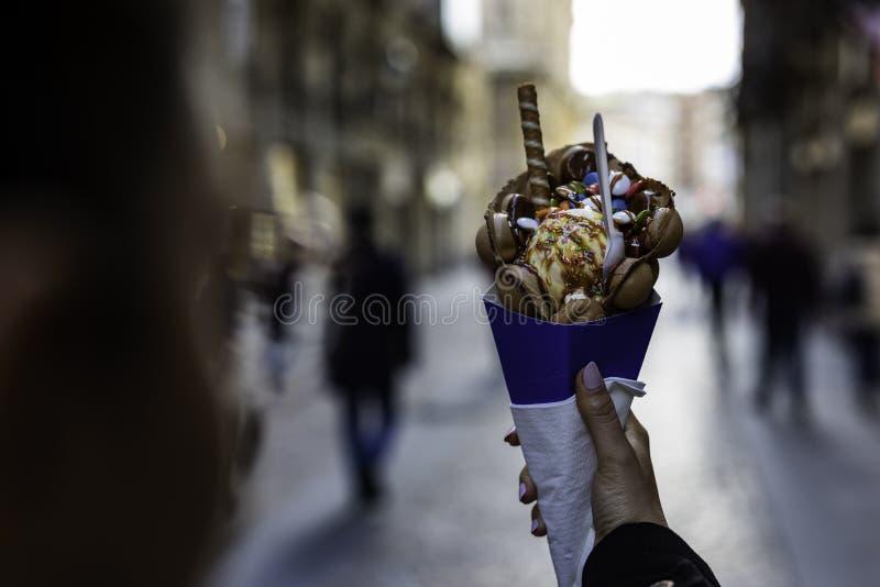 Kvinnahand som rymmer en bubbladillande med glass och godisar på en blå pappers- kotte med den suddiga oigenkännliga folkmassan p arkivfoton