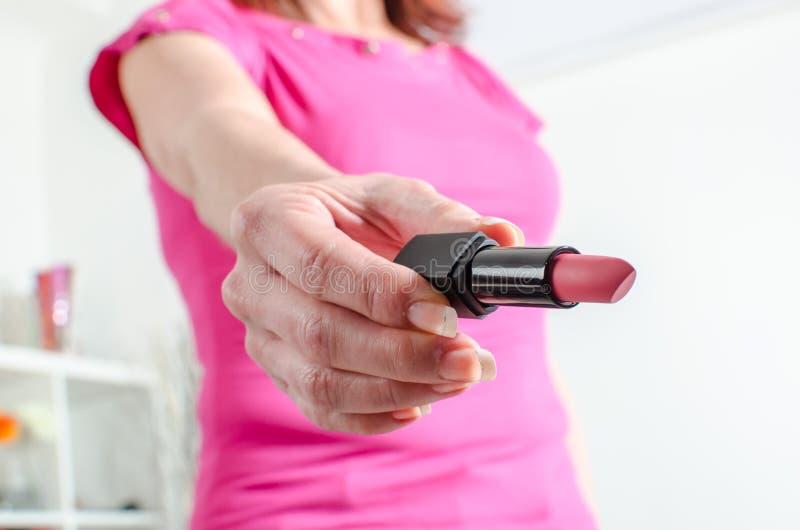 Kvinnahand som rymmer en läppstift arkivfoto