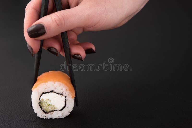 kvinnahand som rymmer en sushirulle fotografering för bildbyråer