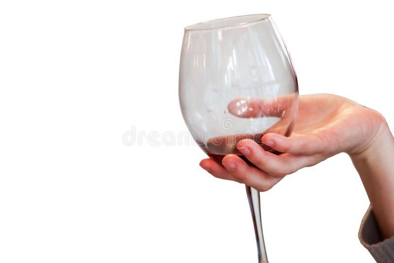 Kvinnahand som rymmer exponeringsglas av rött vin royaltyfri foto