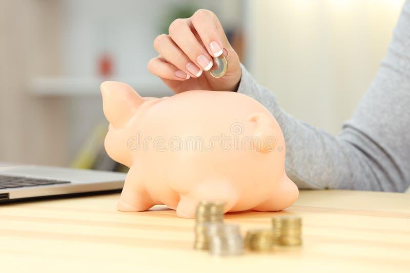 Kvinnahand som sätter ett mynt in i en spargris arkivfoto