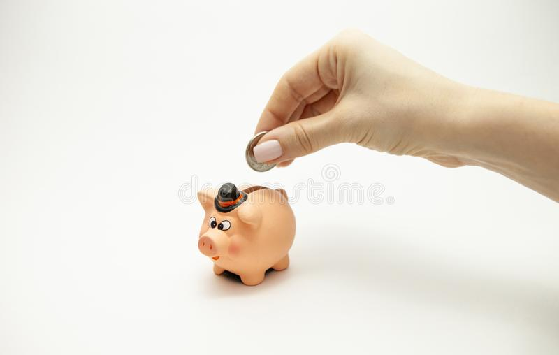 Kvinnahand som sätter myntet in i spargrisen Sparande pengarrikedom och finansiellt begrepp arkivbilder