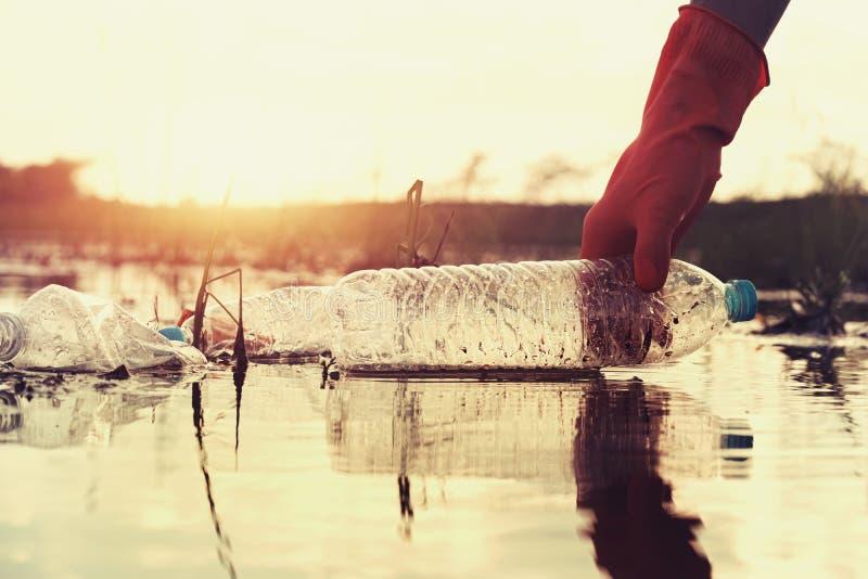 kvinnahand som upp väljer avskräde som är plast- för att göra ren på floden med solnedgång arkivfoto