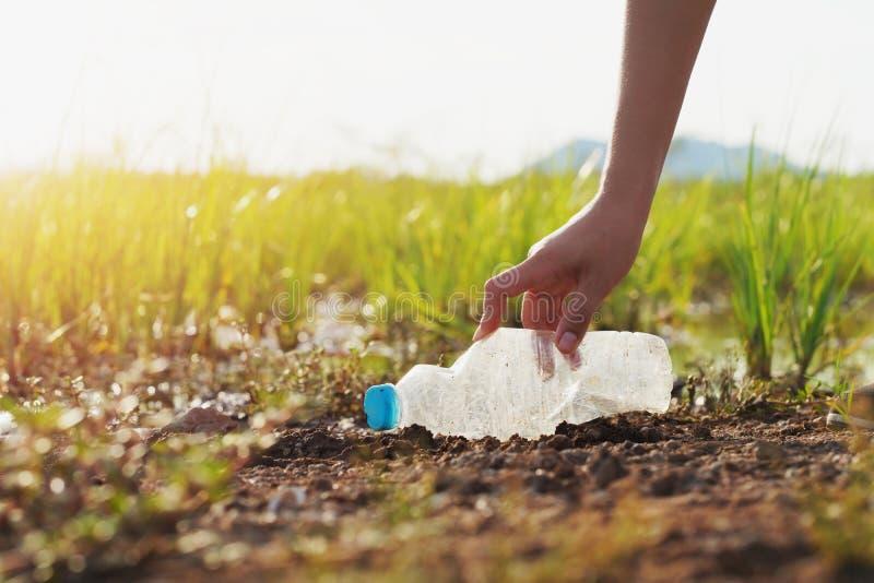 kvinnahand som upp väljer avskrädeplast- för att göra ren på floden arkivfoton