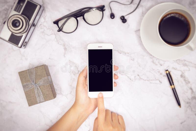 Kvinnahandbruk som är falskt upp av den svarta skärmen för mobiltelefonmellanrum med fingret på pekskärmen med hörluren, penna, k royaltyfria foton