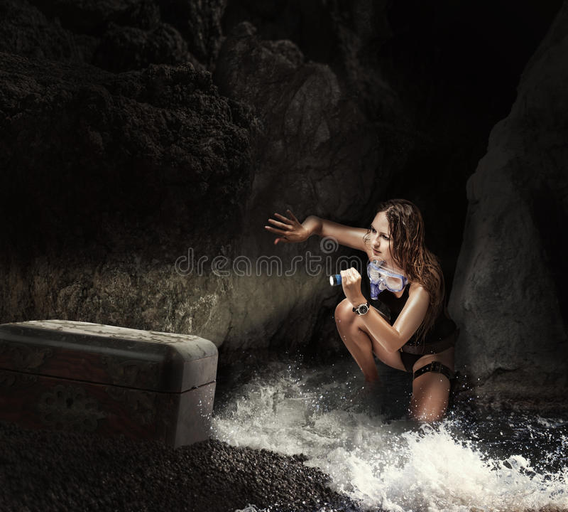Kvinnahandelsresande i havsgrotta med tresurebröstkorgen royaltyfria bilder